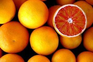 A sliced orange lies face-up on a pile of uncut fruit.