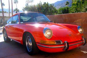 An orange classic 911 Porsche sits in a driveway of a home in Palm Springs, California.