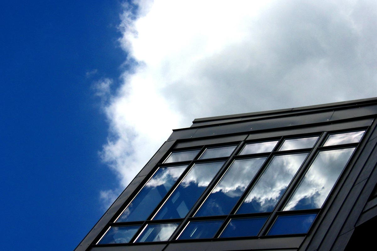 A cloud in a blue sky is reflected in the windows of a modern building.