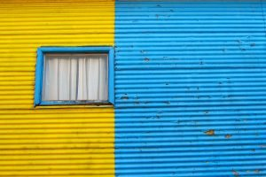 The wall of a house with bright blue and yellow paint in the La Boca neighborhood of Buenos Aires, Argentina.