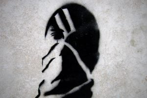 The black and white face of a protester is spray painted on a wall.
