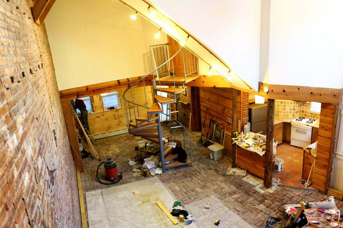 The panoramic view of the basement apartment under renovation with tool and equipment strewn across the floor. As seen from loft bedroom.