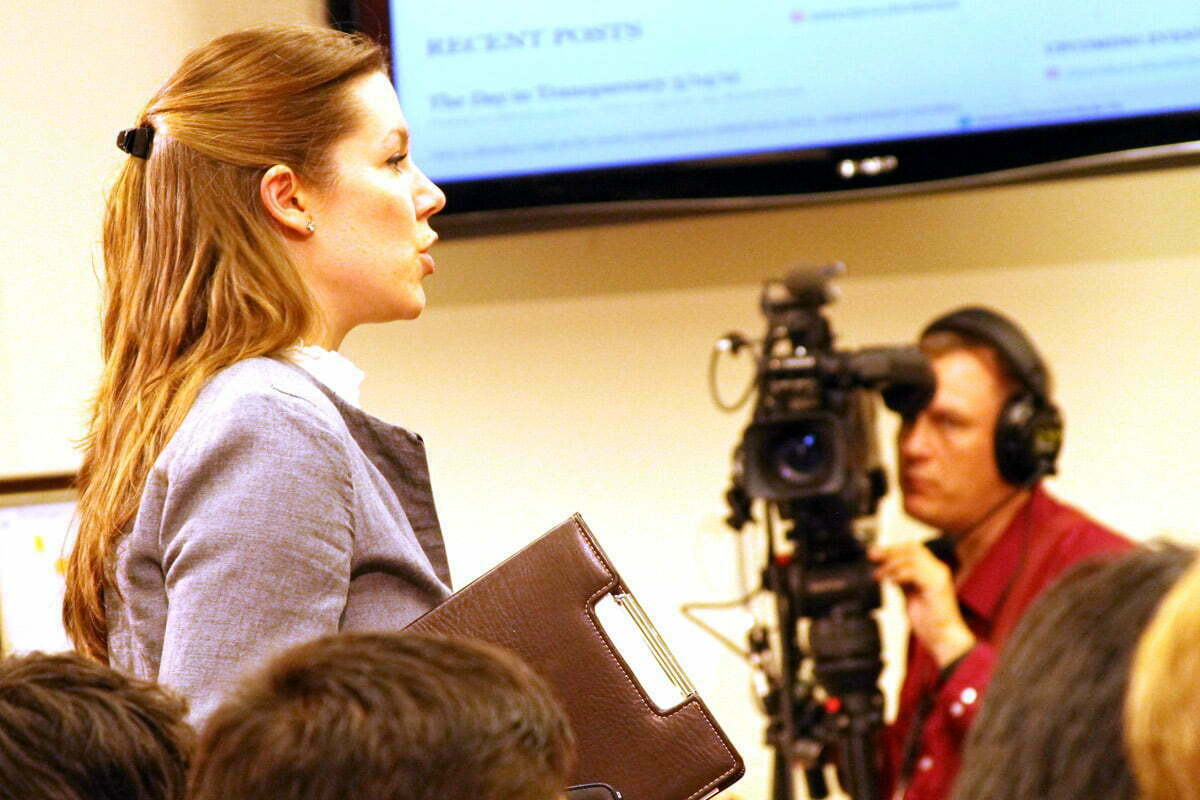 A woman stands to address the crowd with a CSPAN camera in the background.