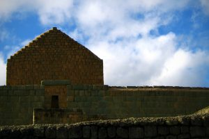 The stone walls of an Incan fort against a cloudy sky.