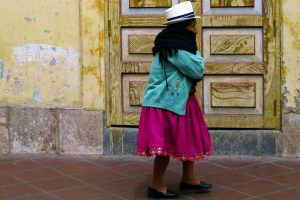 An Ecuadorian woman in traditional colorful dress walks down the street.