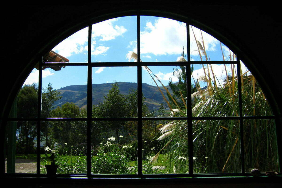 A large window looking out on a beautiful lush garden and mountains in the distance.