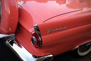 The rear of a classic pink Ford Thunderbird from the 50s or 60s.