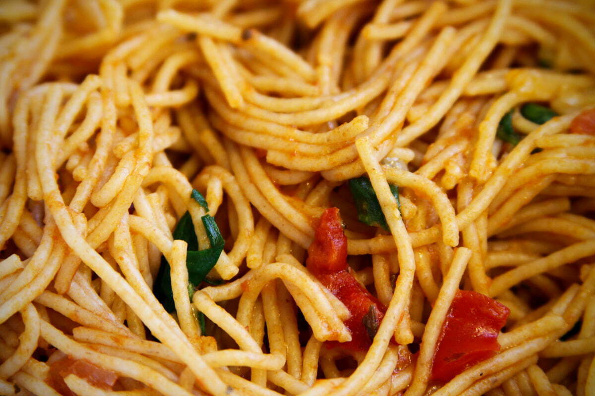 A twisted pile of pasta with bits of herbs, tomatos and peppers.