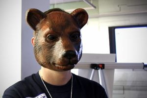 A TransparencyCamp staff member wears a bear mask to scare and entertain campers.