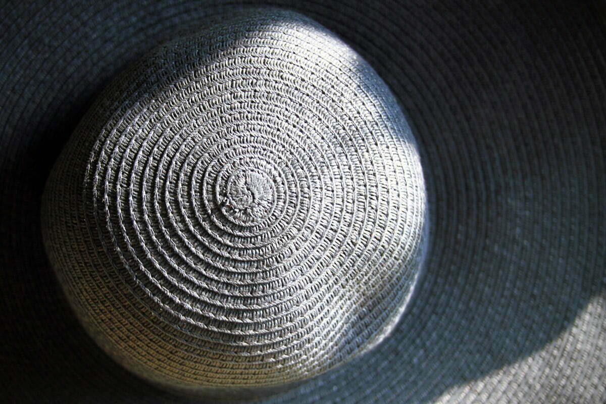 The top of a blue woven derby hat.