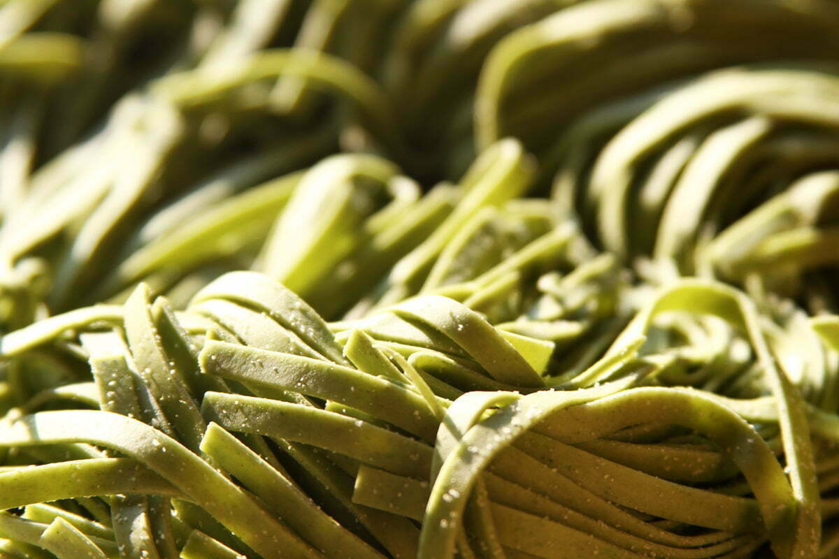 A closeup of a pile of freshly made green pasta.