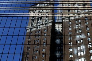An older building and blue sky is reflected in a modern glass skyscraper.