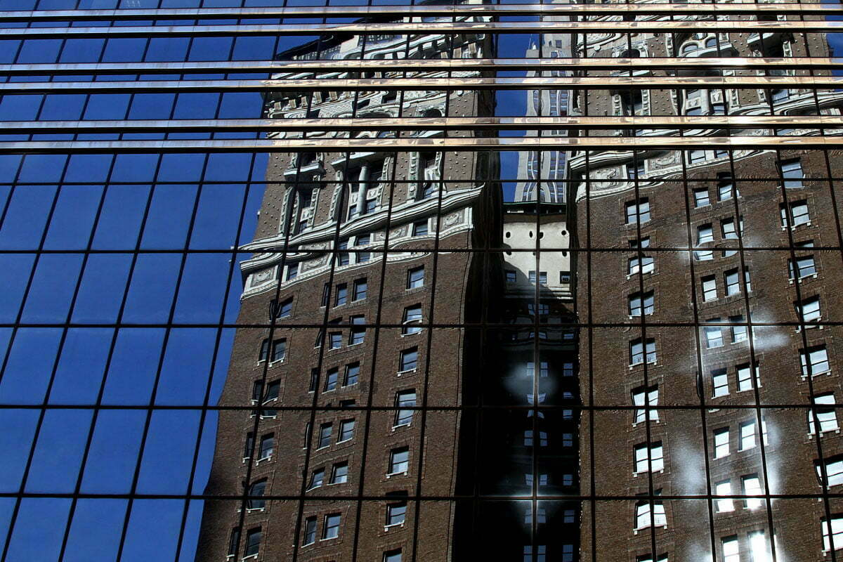 An older building and blue sky is reflected in a modern glass skyscraper in New York City.