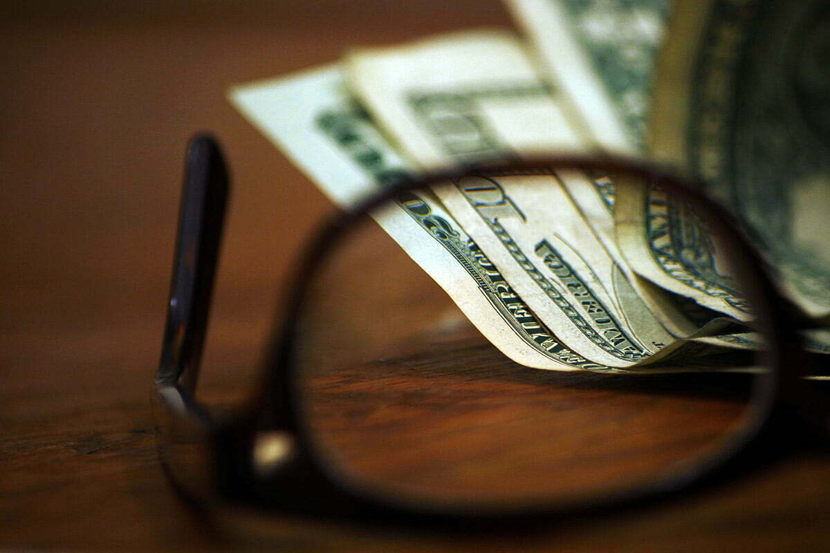 Some dollar bills in focus through a pair of glasses overturned on a desk.
