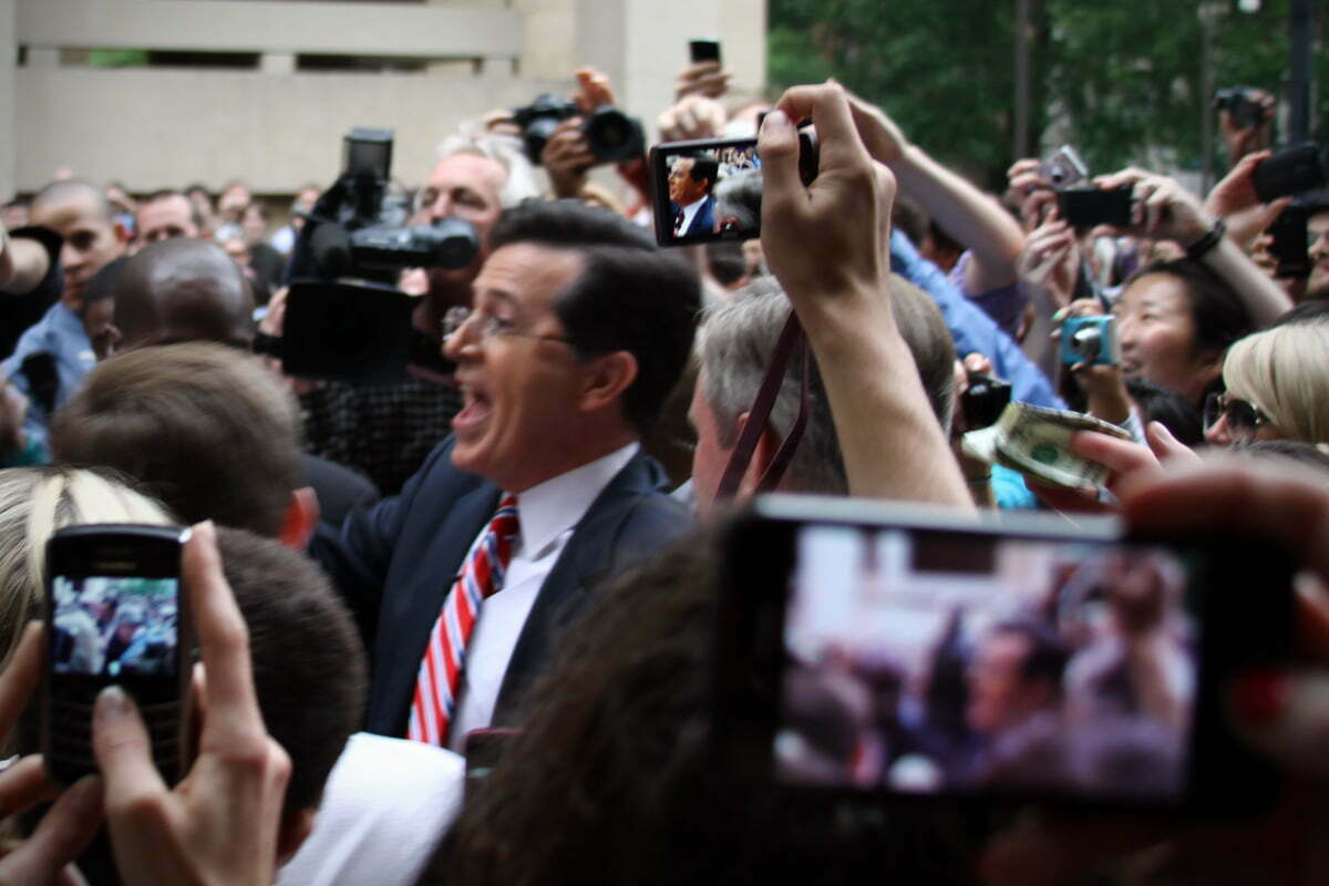 Steven Colbert is surrounded by cameras as he leaves Washington DC