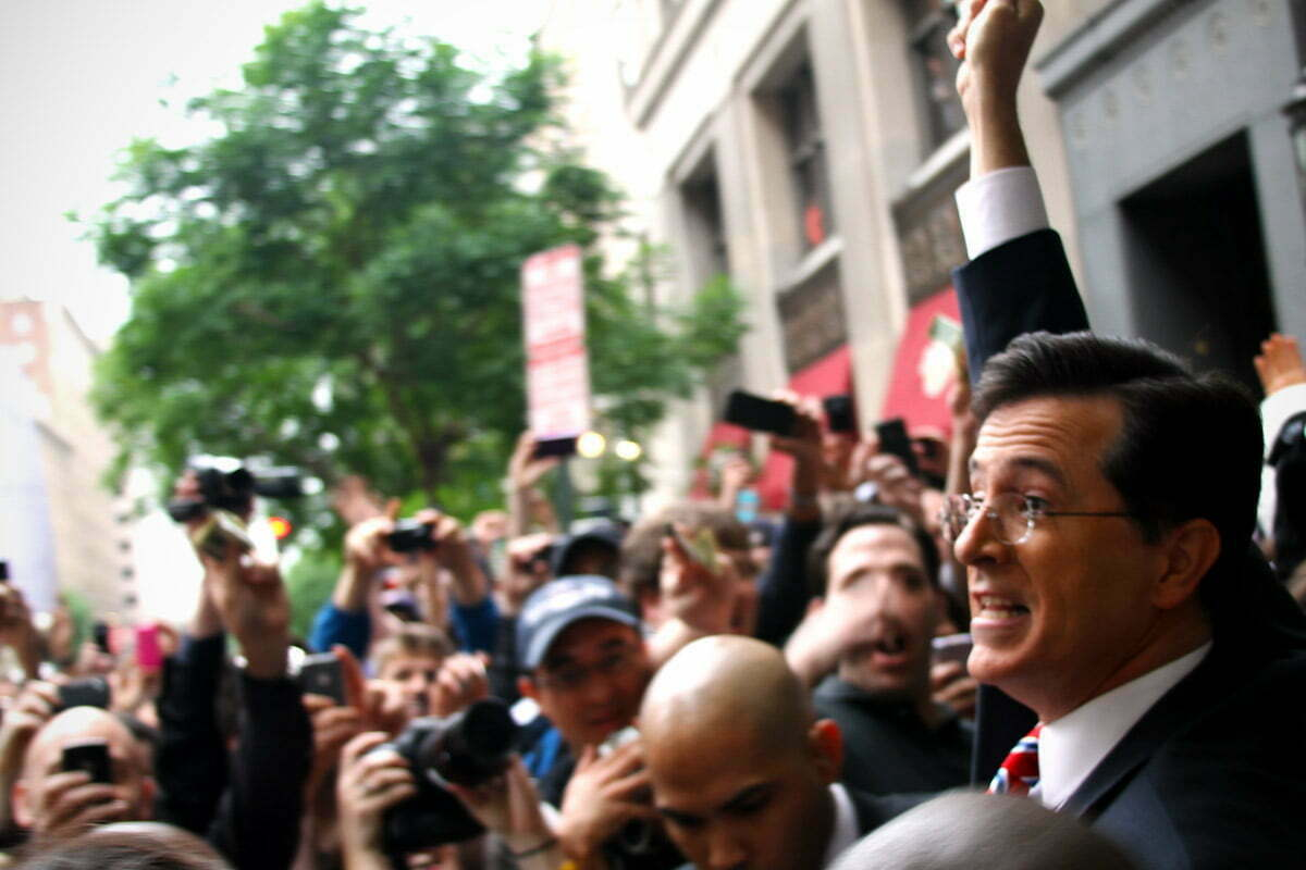 A triumphant Steven Colbert emerges from the FEC in Washington DC and holds money high above the crowd.