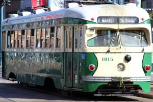 The side view of a green F Market street trolly in San Francisco, California.