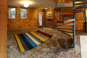 A panoramic photo of the front area of a basement apartment with a large rug and spiral staircase.