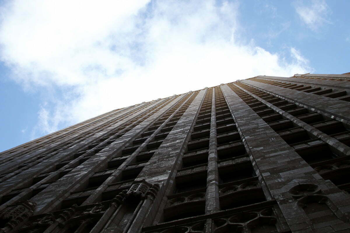A view up the facade of a San Francisco facade at the clouds, sun and sky above.