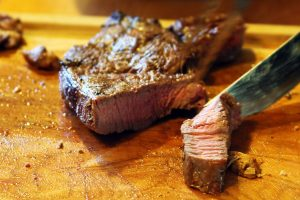 A grilled medium rare steak being sliced open on a wooden cutting board.