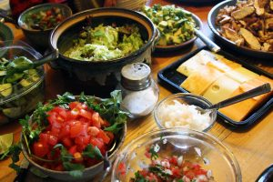 A wooden counter covered in usual taco fixings such as salsa, cheese, tomato, ground beer, grilled chicken, guacamole and lettuce.