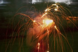 A girl sets off fireworks and a sparkler before Independence Day.