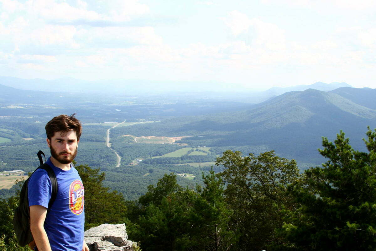 A hiker looks back at the camera over a panoramic view of the Shenandoah Valley.