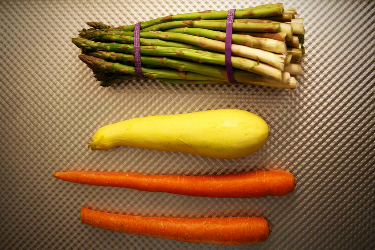 A bundle of asparagus, a single yellow squash and two carrots lie on a pan before cooking preparation begins.