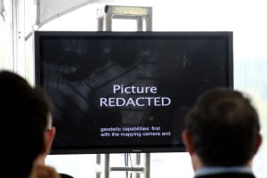 """A video screen showing """"Picture Redacted"""" as a crowd watches."""