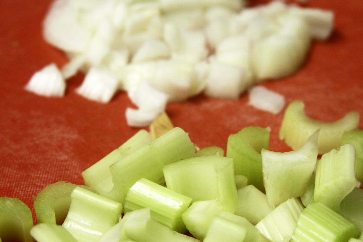 Two distinct piles of chopped celery and onions lie on a red cutting board.