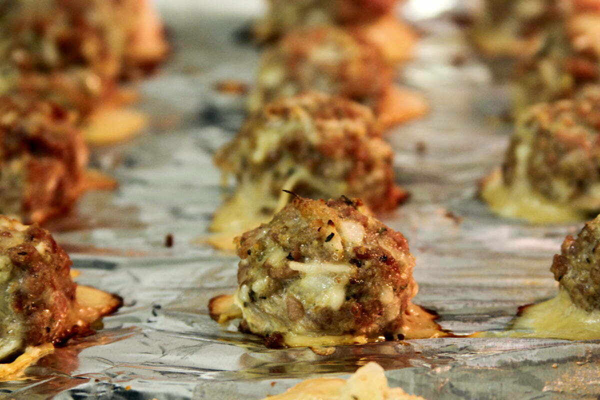 Neatly arranged finished homemade turkey meat balls sit on aluminum foil after coming out of the oven.