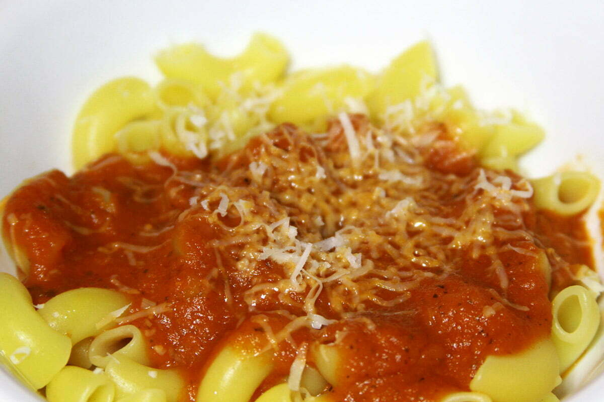 A white bowl of yellow pasta and some red sauce covered in white cheese.