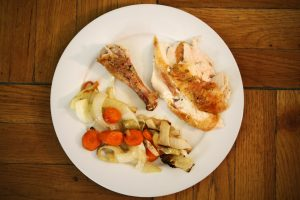 A white plate full of roast chicken with a drumstick and assorted veggies.