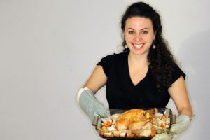 Sally holds the roast chicken with vegetables.