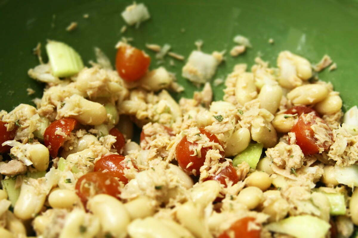 A close-up photo of a tuna salad in a green bowl with tomatos, onions, celery and fresh rosemary.