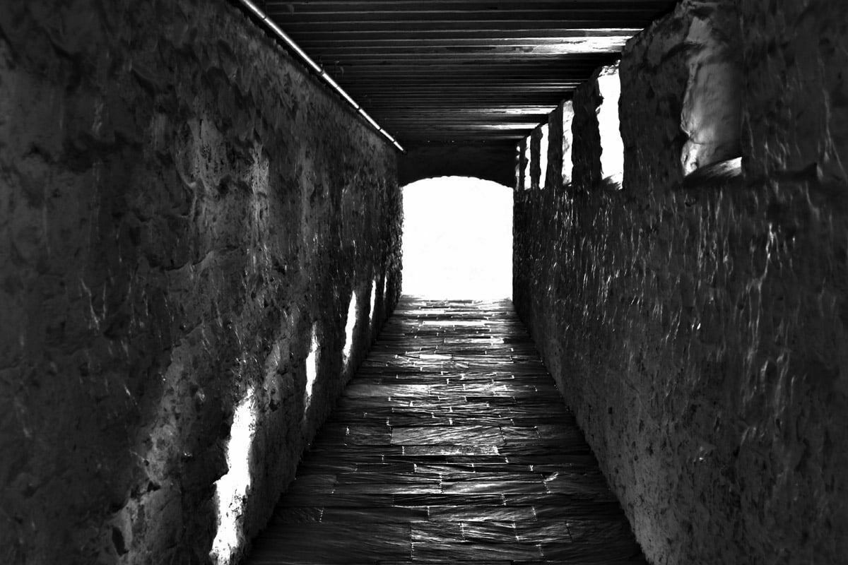 A black and white high dynamic range image of an underground passageway at Monticello. Light from small windows on the right project sunlight on the left side of the hallway and the end of the tunnel is flooded in white light.