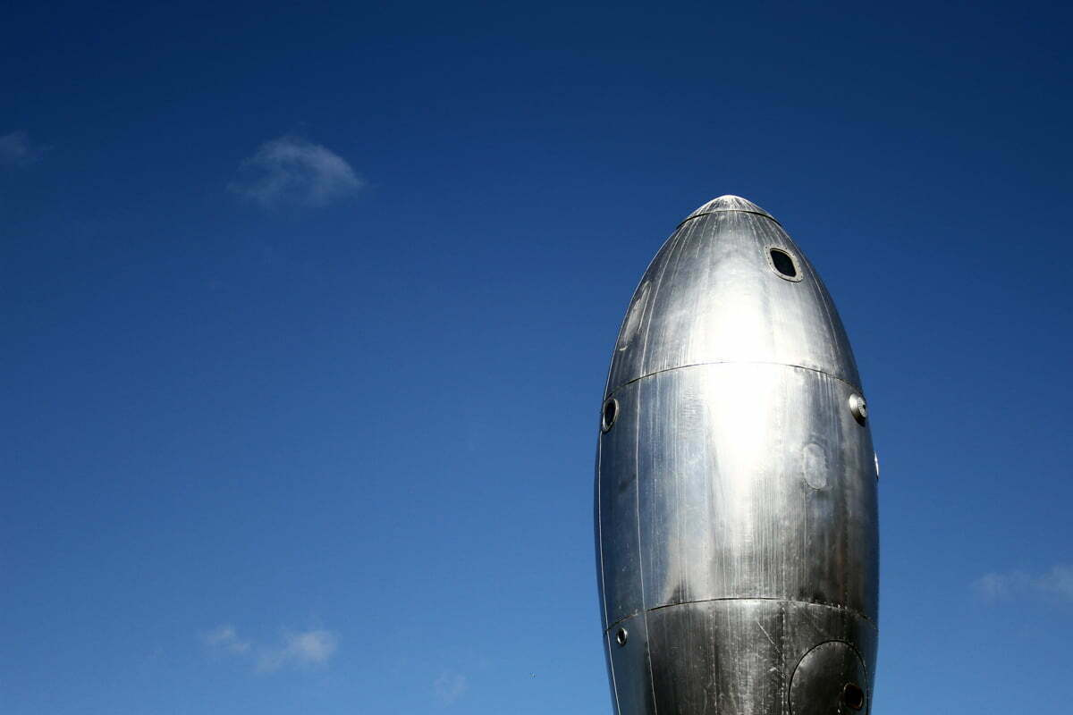The shining metal surface of the Ray gun gothic rocket ship against a blue sky on Pier 14 in San Francisco.