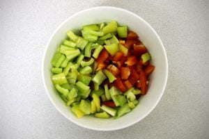 Sliced green peppers and cut red peppers sit in a white bowl.