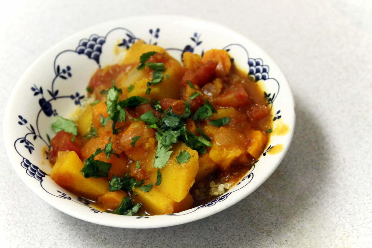 A colorful Moroccan stew sits in a white and blue soup bowl.
