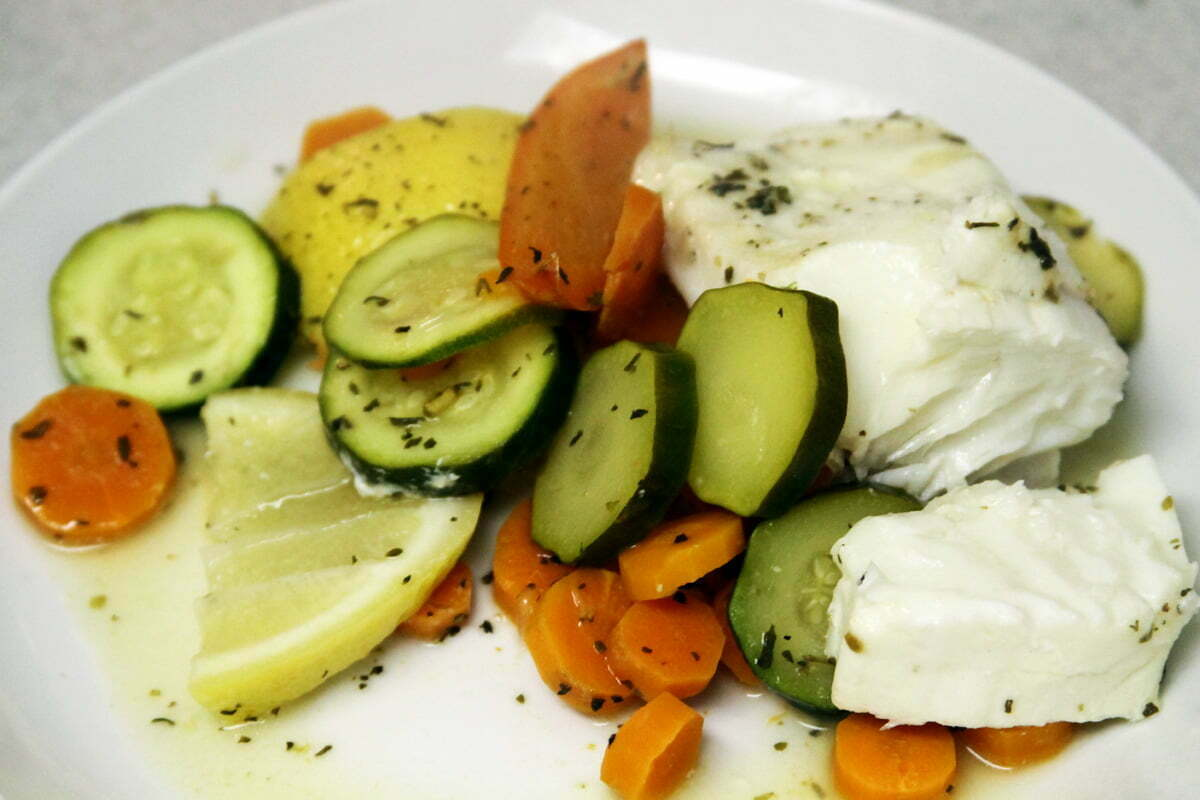 The finished halibut meal sits on a white plate surrounded by cooked veggies including lemons, zucchini and carrots.