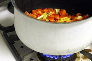 A white pot of colorful chopped veggies sits on the lit burner.