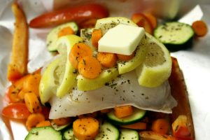 A filet of Halibut sits on some foil covered in lemon slices, carrots, cucumber and butter.