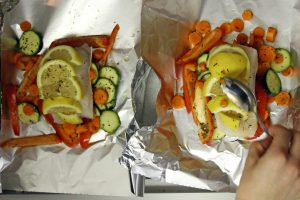 Two pieces of white Halibut fish sit on aluminum foil with colorful lemon wedges, zucchini slices, carrots and red pepper.
