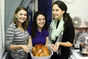 Three friends collectively hold up a thanksgiving turkey for the fakesgiving tradition.