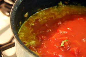 The reddish mixture of spices and tomatos sit on the stovetop to make a spicy Moroccan stew.