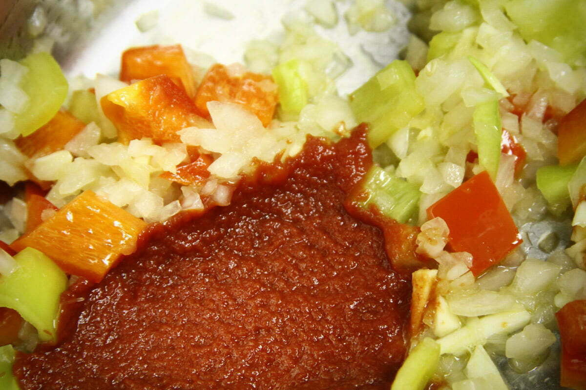 A dash of tomato paste is added to a colorful pile of chopped veggies in a cooking pot.