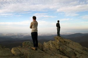 A man and woman face different directions looking out over a panoramic view.