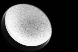 A surreal black and white image of a speckled countertop through a light ring.