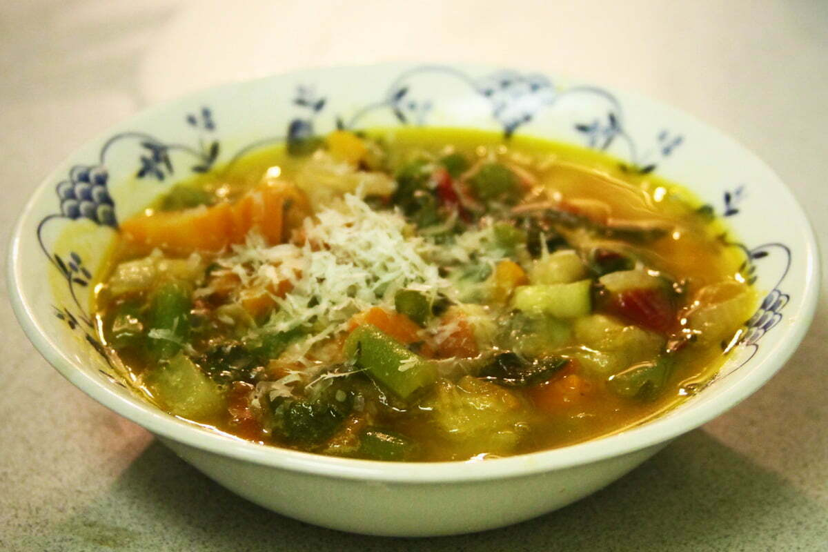 A bowl of momma's veggie soup with some parmesan cheese on top.