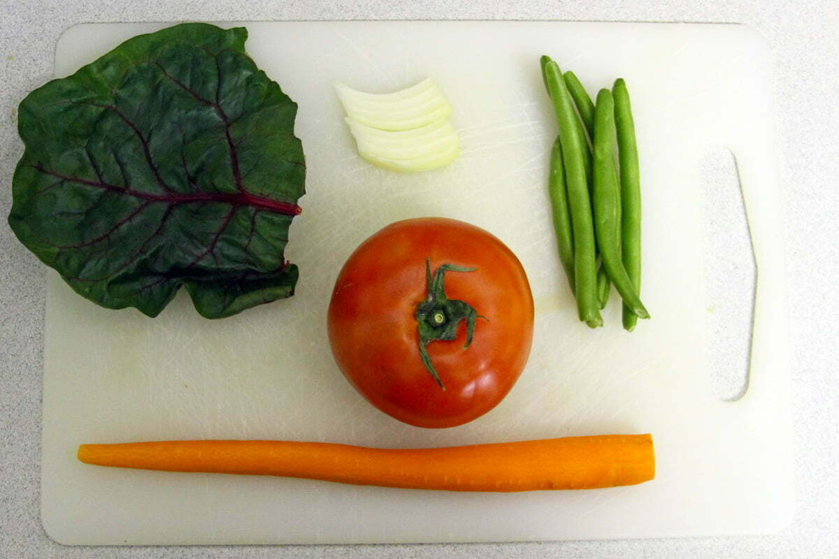 A carrot, tomato, string beans, bits of an onion and a leaf of a ruby chard sit on a white cutting board before being incorporated into a soup.